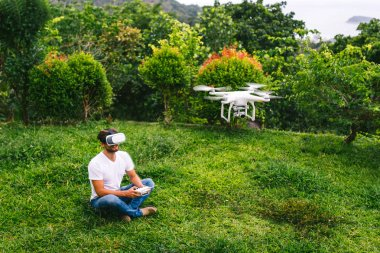 A man in a virtual reality helmet sitting next to the drone
