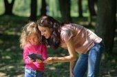 Fényképek Fiatal barna anya bemutatás hogyan használ Smartphone-hoz Her szőke gyermek élvezi meleg napos időjárás kívül a parkban