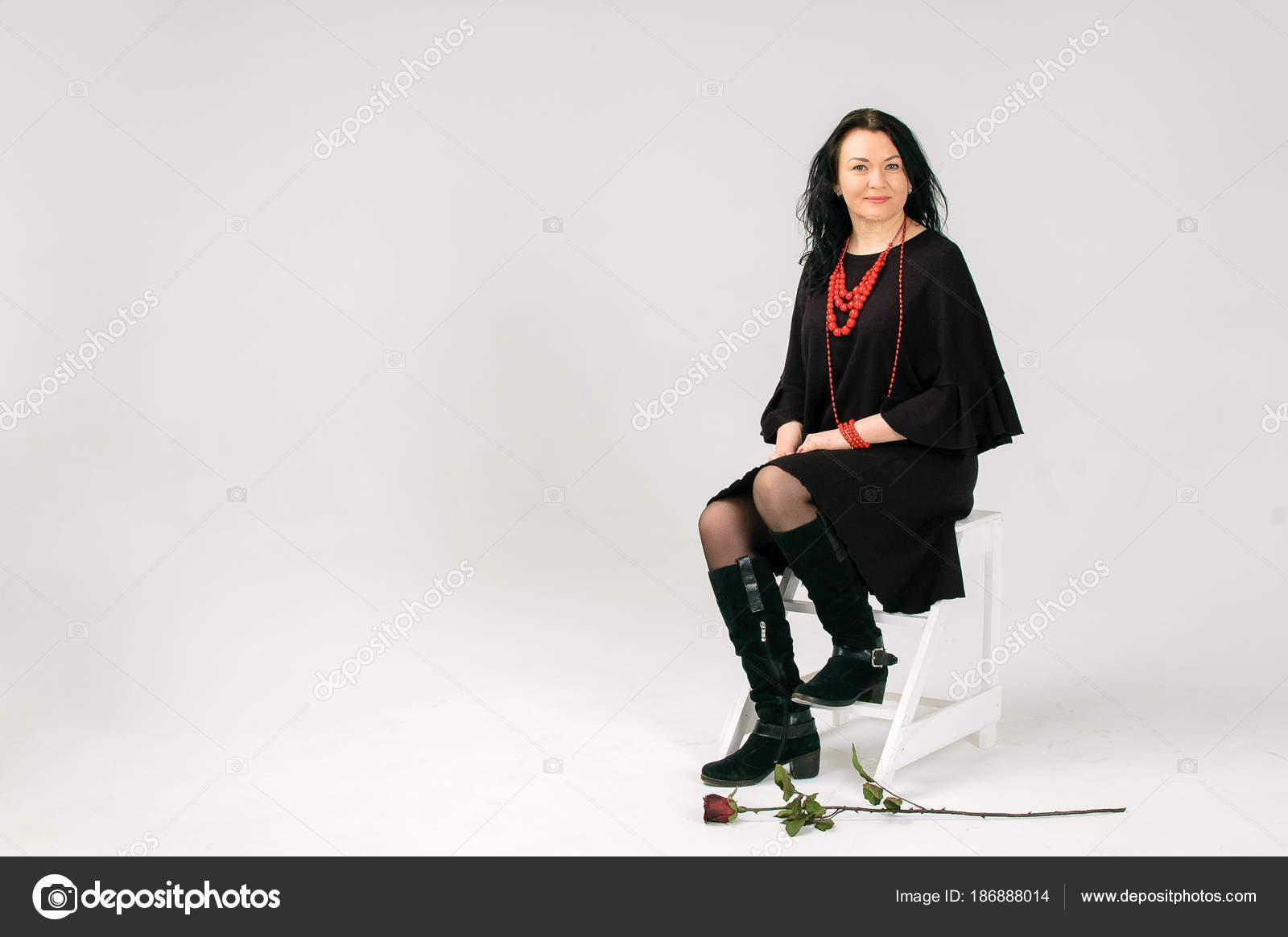 9e47c45bf8f1 Uma linda mulher de cabelos escura de 40 anos em um vestido preto e  vermelhos grânulos étnicos se senta em uma cadeira. Retrato de comprimento  completo ...