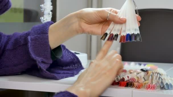 Mladá dívka s krásně upravené ruce a nehty krátké vybere novou barvu pro manikúru v salonu krásy