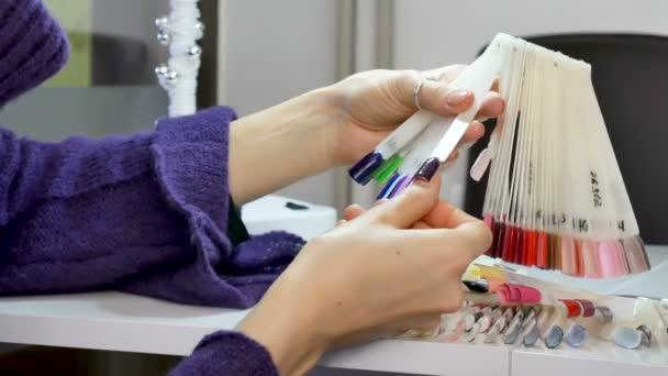 Žena ruce přírodní manikúru a krátké nehty volba ultrafialové nehty vzorek z palety.