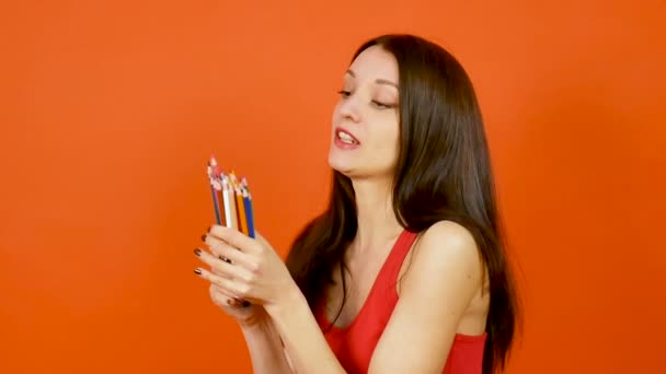 Mladá žena s barevné tužky na oranžové pozadí. Art design