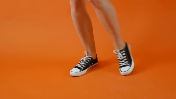 Frauenbeine in schwarz-weißen Turnschuhen tanzen vor hellem Hintergrund im Studio. klassische Schuhe. gesunder Lebensstil, aktive Menschen.