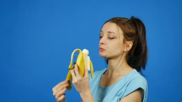 Pretty Brunette Young Woman Holding in Hand Yellow Banana and Then Eating it over Bright Blue Background. Tropical Fruits. Summer Concept. Healthy Eating.