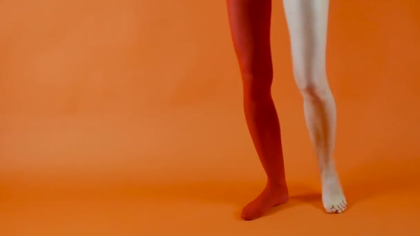 Female model is wearing red tights on the one leg, another leg is naked and without stockings on in studio over bright orange background