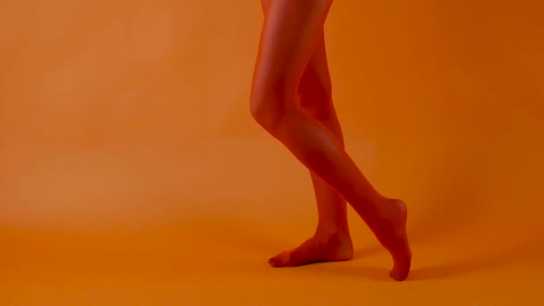 Red stockings on perfect woman legs over bright orange background, female model is dancing in studio