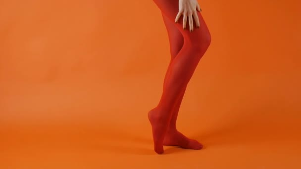 Red stockings on perfect woman long legs over bright orange background in studio