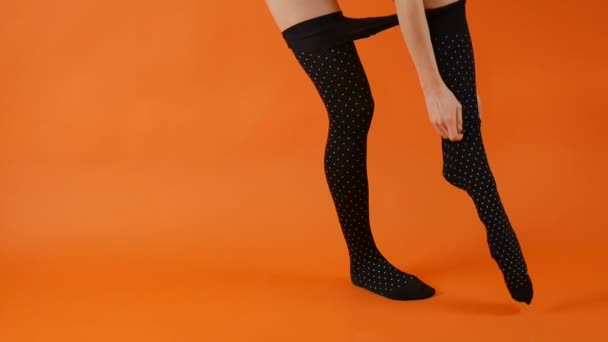 Female model with perfect long legs is wearing black tights on in studio over bright orange background