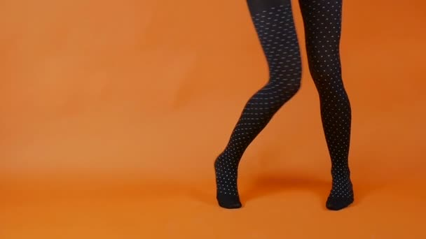 Black stockings on perfect woman legs over bright orange background, female model is dancing in studio