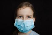Coronavirus Covid-19 járvány. Egy szőke kislány világoskék, eldobható maszkot visel, hogy megvédje a fekete hátterű vírust a stúdióban. Karantén elve