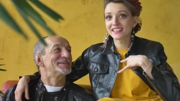 Érzelmi családi portré felnőtt lányról és idősebb apáról a padlásszobában fekete bőrdzsekit visel punk stílusban és egymásra néz, a lány rock and roll gesztust mutat.