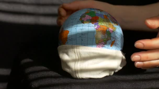 Earth globe with geographical names in Ukrainian cyrillic letters on it dressed in a textile mask in female hands. Coronavirus epidemic in world, Personal protective equipment concept