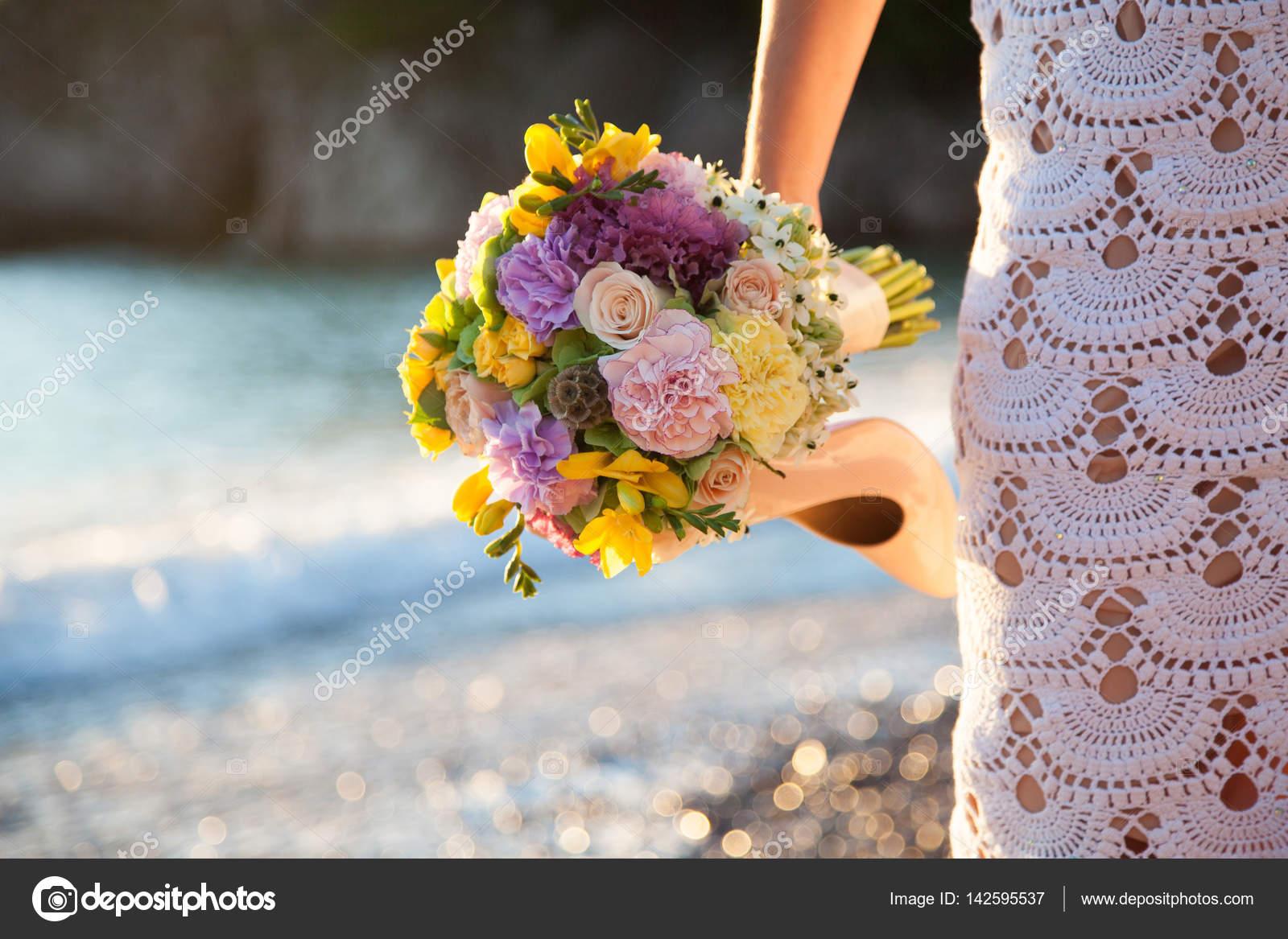Braut wird im weißen Hochzeitskleid am Meeresstrand gestrickt ...