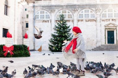 Christmas mood and holidays in Europe. Child girl feeds doves on square. Pigeons flying