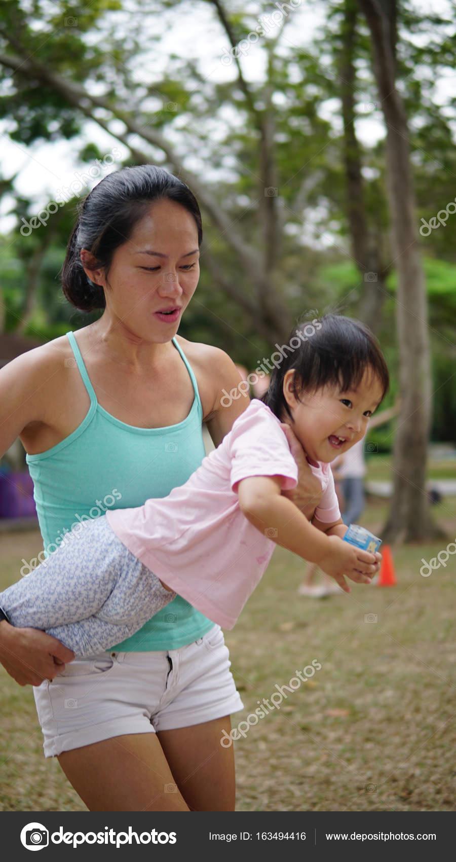 Mujer Asiatica Lleva A Nino Y Participar En Juegos Familiares Al