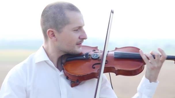 Houslista hraje na housle na skalní plošině