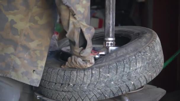 Automechanik montuje pneumatiku na kolo. Zimní pneumatiky