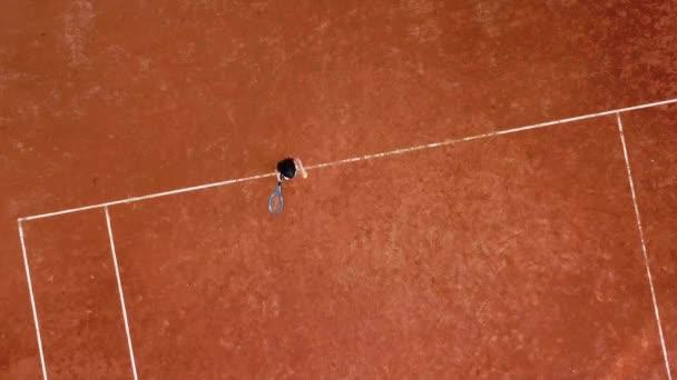 Malá holka tenista odpaluje míč s raketou na tenisovém kurtu. Holčička hraje tenis