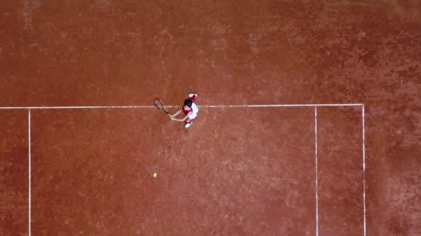 Mladý tenista odpaluje raketový míček na tenisovém kurtu