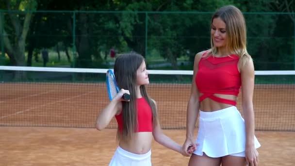 Dospělí a malí tenisté se drží za ruce a stýkají se na tenisovém kurtu. Matka a dcera jsou sportovkyně.
