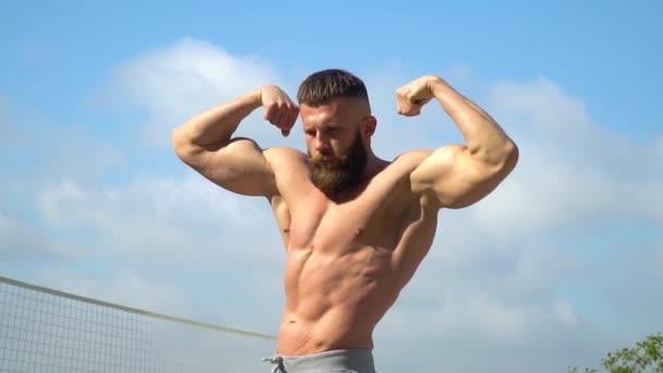 Kulturista demonstruje svaly. Mladý vousatý atletický kulturista hraje sportovní venku