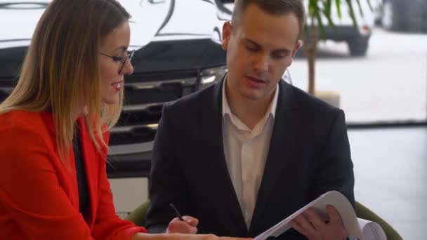 Seller and buyer are studying the contract of sale of the car. Beautiful woman buys a car