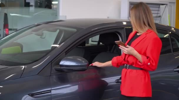 Beautiful woman uses smartphone while sitting in a car at a car dealership