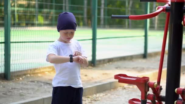 Ein Junge an öffentlichen Trainingsgeräten auf der Straße blickt auf seine Armbanduhr