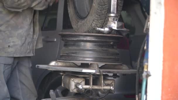 Opravu píchlé pneumatiky z auta mechanikem. Proces vyjmutí pneumatiky z kola ze slitiny pomocí měniče pneumatik. Zimní pneumatiky