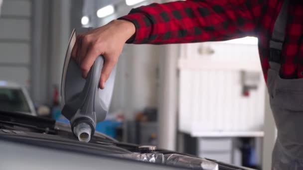 Autószerelő, autószerelő műhelyben. A szerelő olajat önt a motorba.