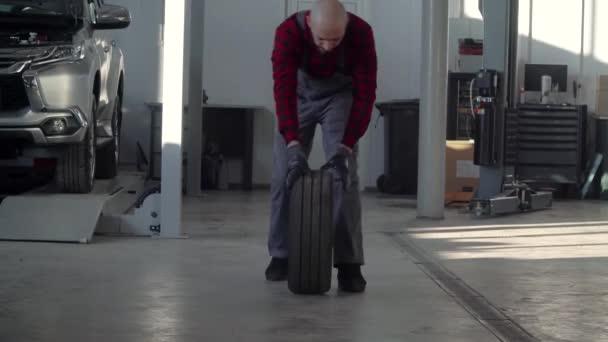 Profesionální mechanik v autoopravně mění kolo na osobním automobilu. Autoservis, opravy a údržba