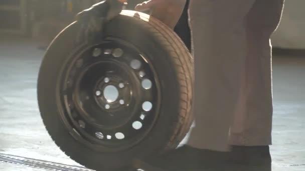 Mechanik drží pneumatiku v garáži. Profesionální mechanik v autoopravně mění kolo na osobním automobilu