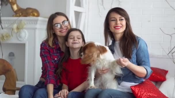 Two women and daughter with dog at studio looking to camera