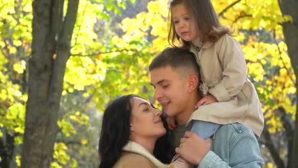Dítě na zádech otce. Šťastná rodina v podzimním parku. Podzim