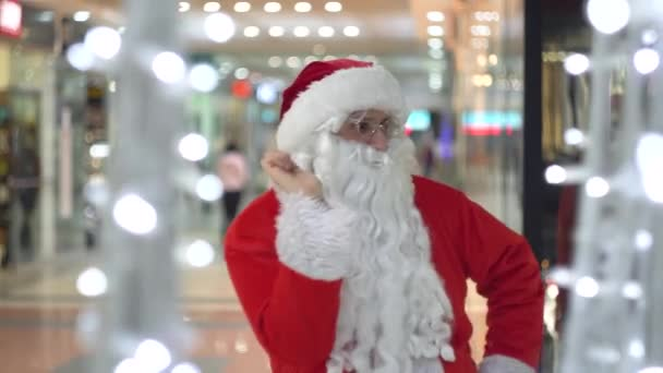Funny Santa Claus dancing in a large shopping center