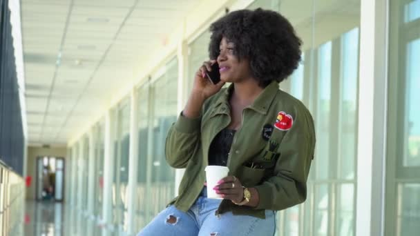 Az afro-amerikai lány a reptéren várja a beszállást és az indulást, és telefonon beszél. A lány kávét iszik a reptéren.