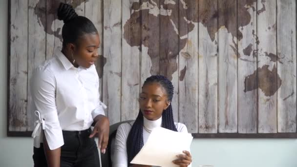 Beautiful african american businesswoman consults her project manager about documents with graphs and statistics