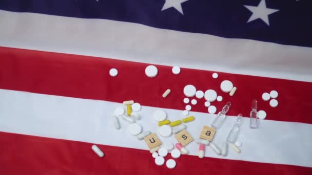 Mixed pills on US flag with the inscription USA. Coronavirus in the USA. US healthcare