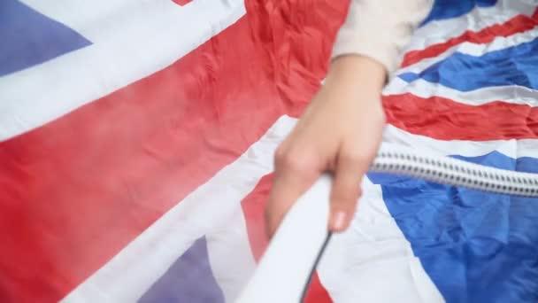 Žena žehlící britskou vlajku s párou. Vánoční přípravy