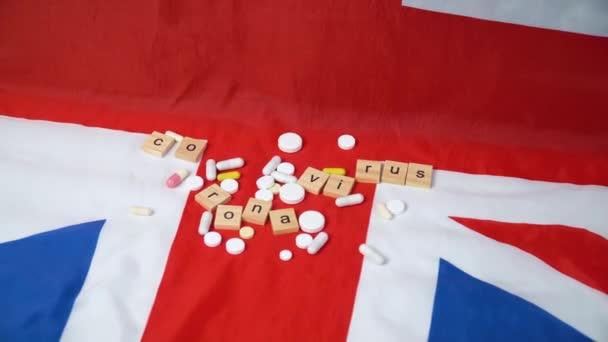 Smíšené pilulky na britské vlajce s nápisem coronavirus. Koronavirus ve Spojeném království. Vítězství nad koronavirem. Covid-19 vakcína