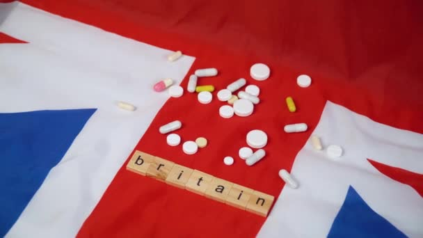 Mixed pills on UK flag with the inscription Britain. UK healthcare