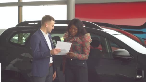 Professional car salesman is telling interested african american buyer about luxurious car in motor show. Auto business, car sale, technology and people concept
