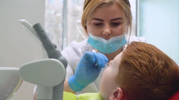 Chlapec na recepci u zubaře v zubním křesle. Dětská stomatologie