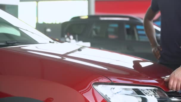 Professional car salesman closes the hood of a car in motor show