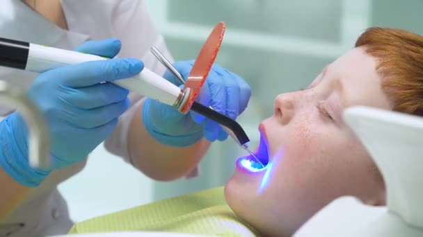 Female dentist in work. Little boy at reception at dentist in dental chair. Pediatric dentistry