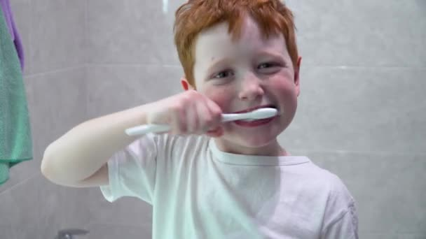 Child brushing teeth in front of mirror in bathroom in the morning