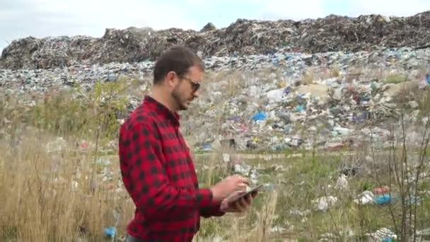 Inspektor skládky odpadků se záznamy o znečištění na skládce ve městě