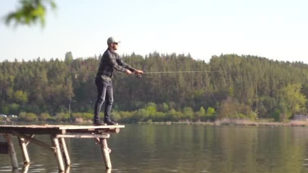 Rybář hodil rybářský prut do jezera nebo říční vody. Rybaření na jezeře