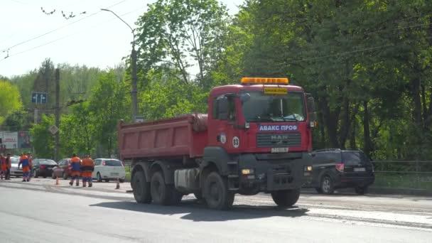 Ternopil, Ukrajina, květen 2020: Tým pracovníků v ochranných uniformách pracuje na výstavbě silnic. Pracovníci dopravní zařízení konstrukce průmyslových strojů