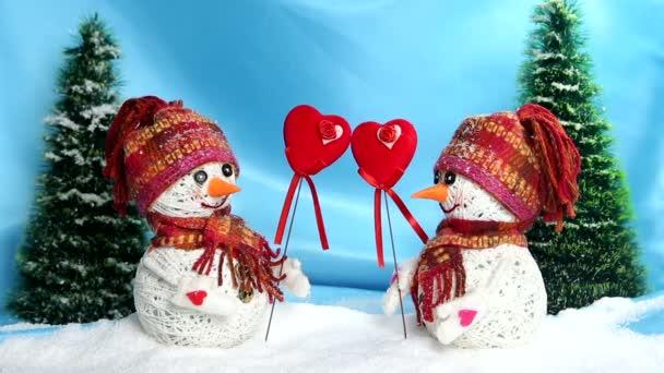 Liebe Schneemänner. Liebe. Valentinstag. Verliebte Schneemänner stehen auf dem Schnee und halten ihre Herzen aus Filz,
